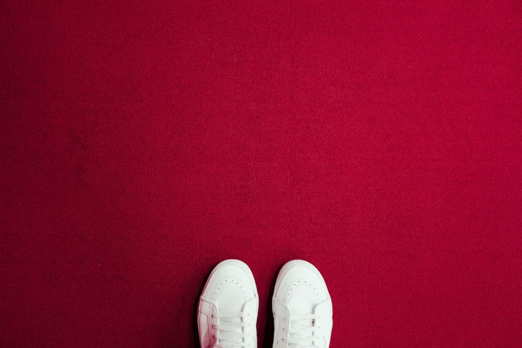Red carpet with a pair of white shoes