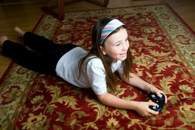 Girl laying on rug using video game controller