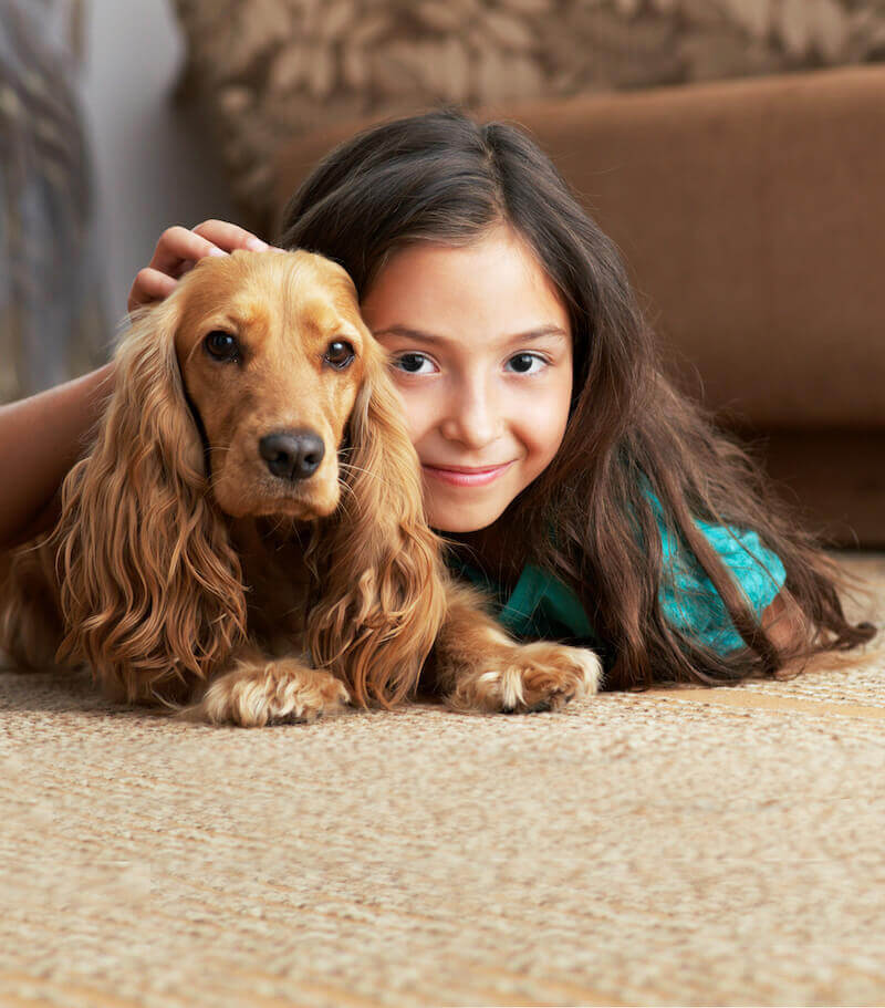girl and dog laying on carpet